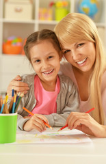 Girl painting with mother