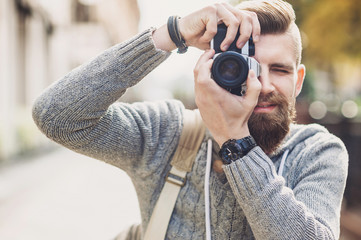 Young cheerful man photographer takes images with camera