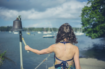 Woman ringing bell to call boatman