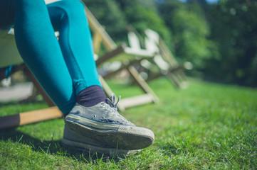 Legs of young woman relaxing in garden
