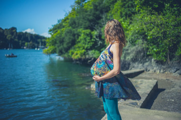 Pregnant woman by water in summer
