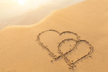 Two hearts drawn in the sand, symbol of love, honeymoon