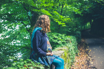 Pregnant woman sitting by roadside in forest