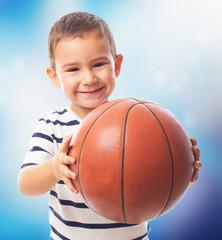 portrait of a little boy holding a basket ball