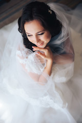 beautiful bride brunette girl in white wedding dress with hairstyle and bright makeup