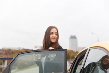 Thoughtful brunette standing at open door of taxi in city