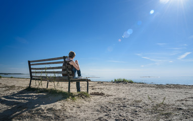 Lonely woman sitting on an old bench at sea coast