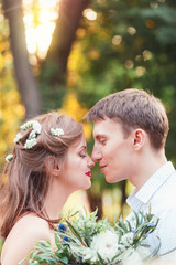 Happy young newlywed couple touching noses in park.Holding a bou