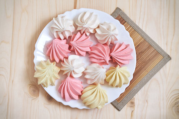 Fresh delicious colored meringue cookies on wooden table. Top view