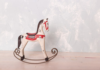 toy rocking  horse on the wooden floor against the backdrop of a