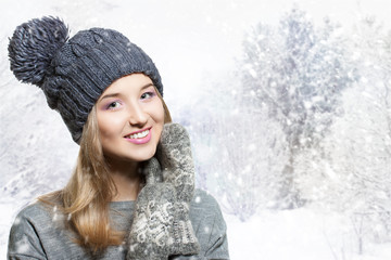 Winter portrait of a young smiling woman in a knitted hat. Winter hat and knitted mittens. cheerful girl snowy background