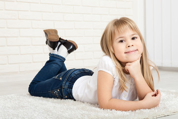 Smiling child girl in cloths lying on floor and relaxing