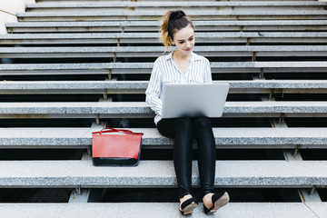 Businesswoman working on a laptop outdoors