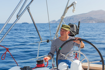 Man drives sailing yacht at the sea. Luxery boats.