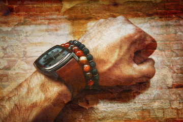 double exposure - brick wall and the man's hand with a watch and bracelets close-up