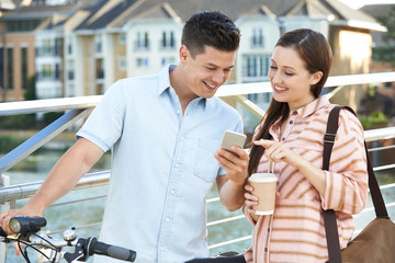 Young Couple Looking At Phone On Way To Work In Urban Setting
