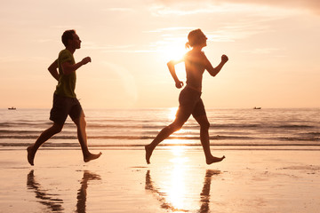 silhouette of beautiful couple jogging on sea beach at sunset, healthy lifestyle concept
