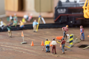 Construction toy / View of construction site of mini toy worker on wood background.