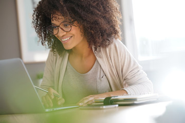 Mixed race woman working from home on laptop computer