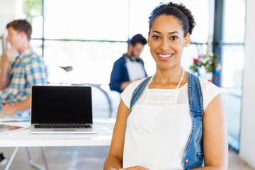 Portrait of smiling afro-american office worker in offfice with her colleagues