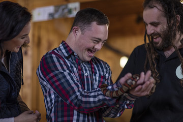 Animal attendant handing over coral snake to young man with down syndrome