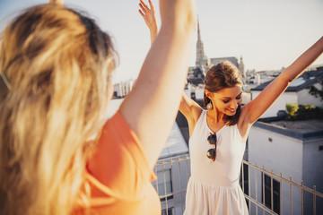 Austria, Vienna, two women dancing on roof terrace