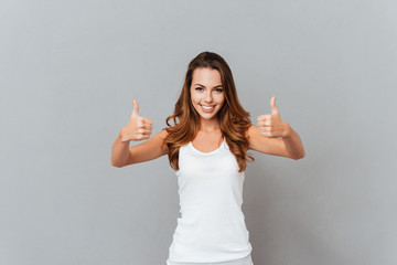Portrait of a casual smiling young woman showing thumbs up