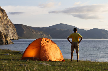 Tourist near a tent in the morning on the lake