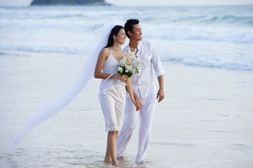 Bride and groom walking on beach, holding hands, looking away