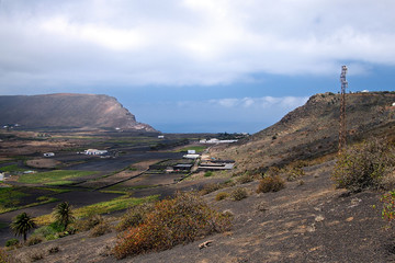 Mountain valley with white buildings and villages between old volcanic slopes. Red Earth and green fields on the background of deep blue sky with white clouds. Lanzarote, Canary Islands, Spain