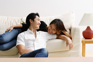 Woman lying on sofa, man sitting on floor in front of her, smiling