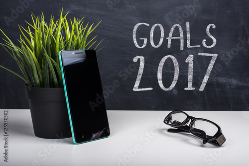 """Modern smartphone and blackboard with motivational text """"GOALS 2017 ..."""