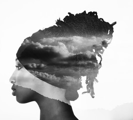 Monochrome double exposure of profile woman portrait and cloudscape