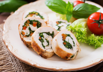Chicken rolls with greens, garnished with salad.