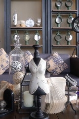 Vintage small mannequin in cozy designer studio with antique collections and blur bookshelf on the background