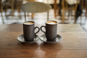 Hot latte art with  black glass on wooden table
