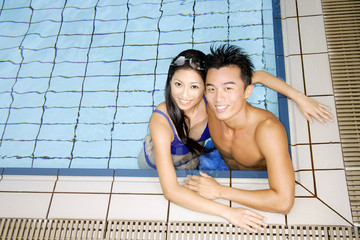 Couple in swimming pool corner, looking up at camera