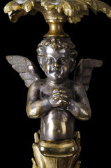 Praying brass angel on black background. A winged putto made of brass, covered with silver, as part of a candelabra from the nineteenth century and a symbol for religious passion. Macro object photo.