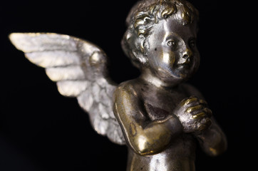 Praying brass angel side view over black. A winged putto made of brass, covered with silver, as part of a candelabra from the nineteenth century and a symbol for religious passion. Macro object photo.