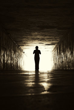 Silhouette of woman in a tunnel