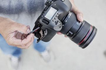 Fotograf wechselt die Speicherkarte, CF-Karte,seiner Digitalkamera