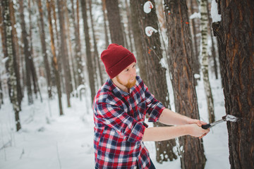 bearded man with an hatchet in the winter forest