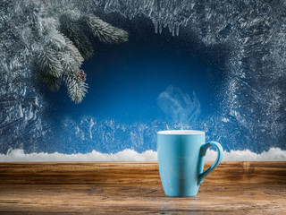 Cup of hot tea, frozen window and Christmas tree against it.
