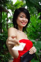 Woman in red tube top, holding credit card towards camera