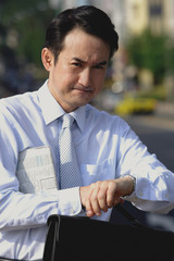 Businessman with newspaper under his arm, looking at watch, frowning