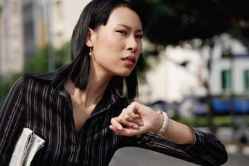 Businesswoman checking the time, frowning