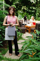 One woman standing on garden path, holding shopping bags