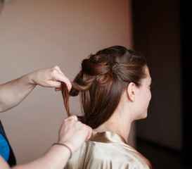 hairdresser makes the bride hairstyle in wedding morning