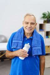 lächelnder älterer mann nach dem training mit trinkflasche