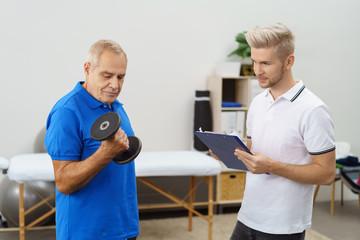 älterer mann trainiert seine arme in der physiotherapie